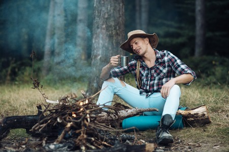 Tourism and hiking concept. Man hiking with overnight stay or picnic. Guy in hat sits near bonfire , trees on background, defocused. Tourist with smiling face relaxing and drinking out of iron mug.