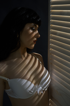 Woman with mysterious face in white bra or lingerie stands behind jalousie. Girl with strips of light and shadows on her body. Erotic and attraction concept. Sexy lady with brunette hair in underwear.