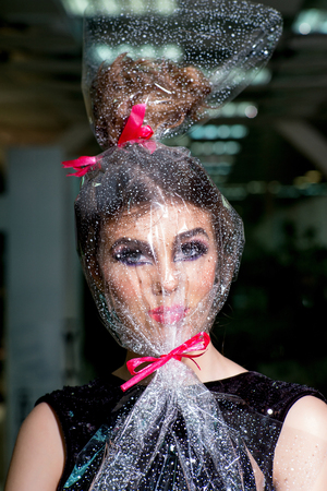 Pack, package, holiday celebration, preparation. Woman face makeup wrapped in overwrap, pack. Girl with transparent wrapper on face, present. Beauty, look, make up, visage. Present, gift, design.