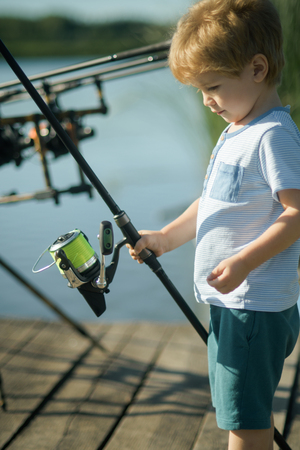 Fishing, angling, activity, adventure, sport. Child with fishing rod on wooden pier. Summer vacation, hobby, lifestyle. Little boy learn to catch fish in lake or river. Childhood, education, training.