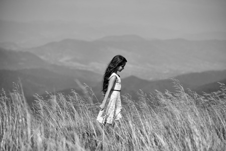 Back viev of young pretty girl in lace summer dress walking in mountain valley with deep dry spikelet grass in spring sunny day outdoor on natural background black and white, horizontal picture
