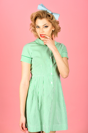Beautiful young woman with pin-up make-up and hairstyle posing over pink background. Banque d'images