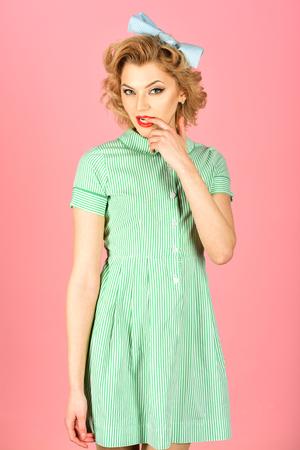 Belle jeune femme avec du maquillage et une coiffure pin up posant sur fond rose.