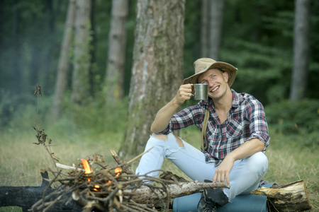 Guy in hat sits near bonfire , trees on background, defocused. Tourist with smiling face relaxing and drinking out of iron mug. Tourism and hiking concept. Man hiking with overnight stay or picnic. Stock Photo