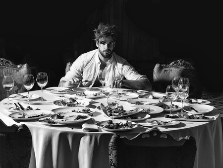 Handsome man with beard and blond messy hair eats with fork and knife at table with leftovers or residues food on dirty plates after banquet dinner in restaurant on dark background