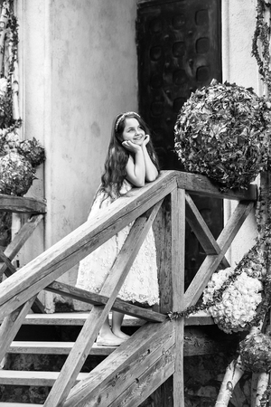 Pretty little girl in dress and wreath with long brunette hair and smiling face standing on wooden stairs near floral decoration outdoor