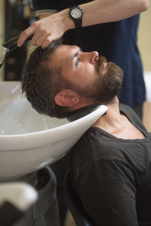 Hipster getting groomed in hair salon. Bearded man mustache in barber shop. Beard fashion, style, trend. Hair wash, care, cut, shampoo. Grooming, shaving, spa.