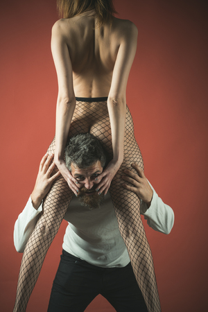 Female in fishnet tights on mans neck, burgundy background. Woman holds male face, man in trap. Dependence by woman concept. Man with screaming face overcomes pain, holds female body.