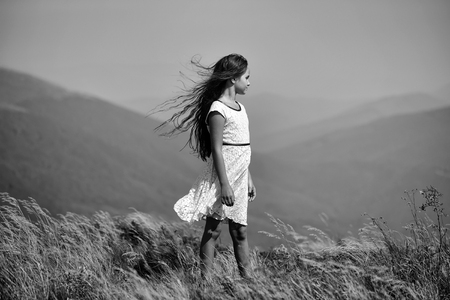 Little cute brunette girl in white lace summer dress looking away standing in mountain valley with deep dry spikelet grass sunny windy day outdoor on natural blue background, horizontal picture Archivio Fotografico - 97502733