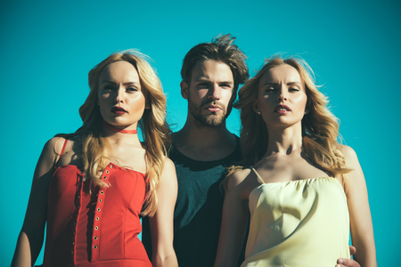 Twins women with macho on blue sky background. Family trust, polygamy, betrayal, swinger. Love triangle and romance. Beauty and summer fashion. Man with beard with twins, relations. friendship