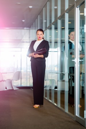 Business and success. Woman in formal outfit in glass office. Manager girl with serious face hold document. Businesswoman or ceo fashion. Modern life and agile business.