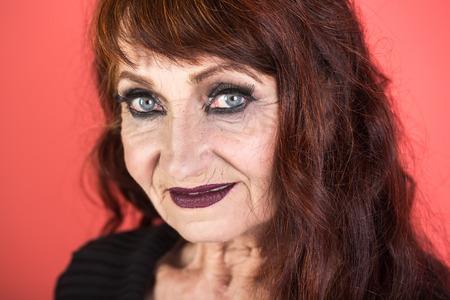Elderly woman with dark hair, deep wrinkles on the face.