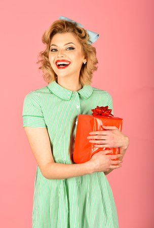 Boxing day, black Friday, birthday. Retro woman with present box, pinup. Happy holiday, celebration, vintage party. Shopping and sale, cyber Monday. Sexy blond girl with retro makeup hold present box. Stock Photo