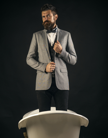 高品質の衛生陶器のコンセプト。スーツを着た厳格な顔をした男は浴槽に立っている。豪華な昔ながらのバスタブにスタイリッシュな外観のヒップ