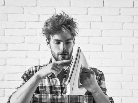 Young handsome man in stylish plaid shirt touches white iron with his finger. Boy with messy hair is about to do ironing Stok Fotoğraf