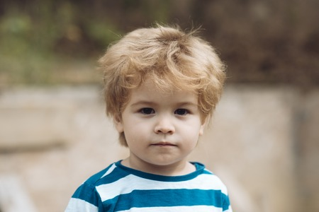 Child or boy with serious face wears striped clothes. Childhood concept. Cute, adorable kid or son with untidy blonde hair on light background, defocused.