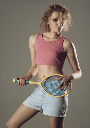 Girl with untidy hair play with tennis racquet like guitar. Sport and fun concept. Woman coach with smiling face has fun after hard training, grey background. Fitness trainer holds tennis racquet. Stock Photo