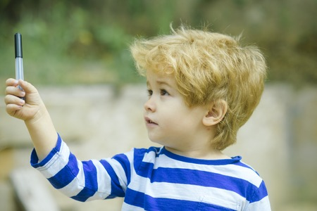 Boy holds or plays with pen or marker in hand. Child or boy with busy face wears striped clothes. Childhood concept. Cute, adorable kid or son with untidy blonde hair on light background, defocused.