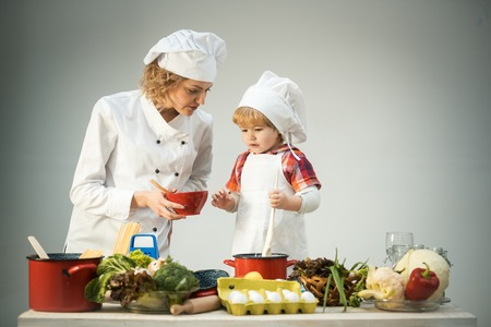 Chef and assistant near kitchen equipment and food products. Happy family mom teaching cute boy preparing and cooking healthy salad for first time. first lesson and healthy lifestyle concept.