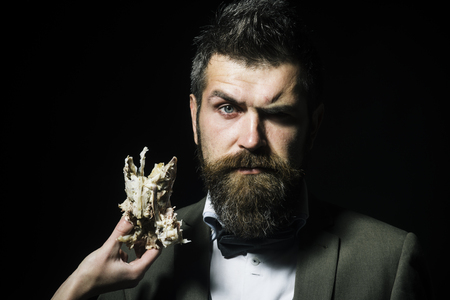 Man with beard and mustache wears bow tie on black background. Hipster with grimace on face near bones or skeleton of chicken. Masculinity and brutality concept. Female hand holds chickens skeleton. Archivio Fotografico