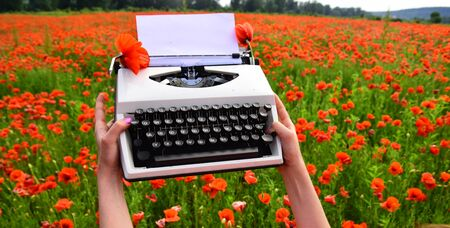 Hand holding a vintage typewriter in a poppy field.