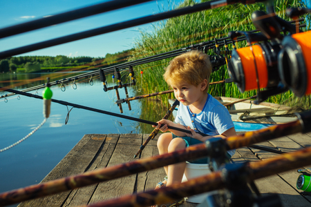 Adorable baby on river with fishing rod and fishing Stock fotó