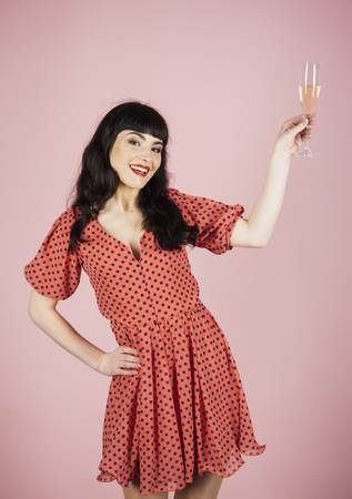 Birthday, party, positive emotion, anniversary, wishes, greeting concept. Happy girl with cheerful face on pink background. Woman drinks champagne and smiles. Lady wears dress and holds wine glass.