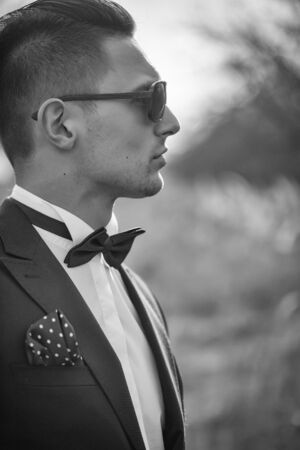 Handsome young groom in wedding suit with bow tie in sunglasses sunny day outdoor Stock Photo