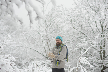 skincare and beard care in winter. Winter sport and rest, Christmas. Man in thermal jacket, beard warm in winter. Temperature, freezing, cold snap, snowfall. Bearded man with skates in snowy forest. Stock Photo