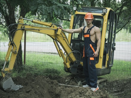 Sexy man with nude torso near construction equipment or excavator on background. Sexy builder concept. Handsome man or bodybuilder with big muscles. Muscular builder in hard hat wears overalls.