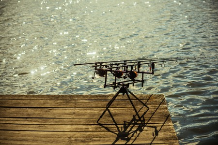 Spin fishing, angling, catching fish. Spinning tackles on pod on wooden pier. Fishing, adventure, sport, activity. Rods and reels at river or lake water. Summer vacation, pastime, hobby. Stock Photo