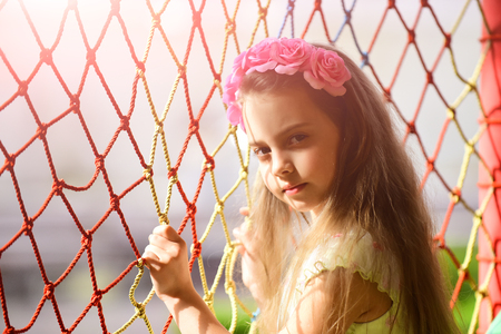 Fashion, spring, look. Girl child with pink flowers in hair spring. summer fashion, beauty salon. Hairdresser and hairstyle. Little girl with flower in hair at net, childhood and happiness.