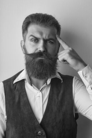 bearded man, long beard, brutal caucasian hipster with moustache with serious face in shirt and brown waistcoat on white background, unshaven guy with stylish hair getting haircut with raised hand
