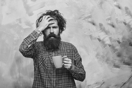 Bearded man, caucasian hipster, with long beard, moustache and stylish fringe hair, haircut, on face in red plaid shirt holding blue cup on abstract pink wall background