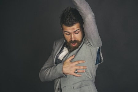 Man with beard wears jacket with hole on dark background. Surprised guy bought counterfeit or fake brand. Hipster chose small size jacket, seam torn under armpit. Bad quality of clothes concept.