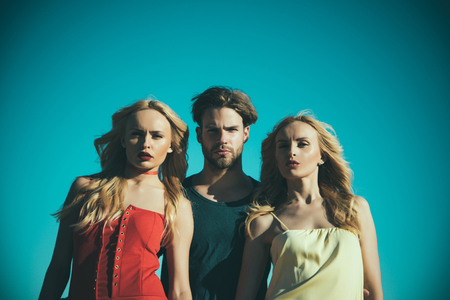Man with beard with twins, relations. Twins women with macho on blue sky background. Love triangle and romance. Family trust, polygamy, betrayal, swinger. Beauty and summer fashion. friendship
