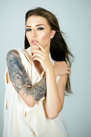 Woman with tattoo painting, fashion. Woman with long brunette hair, hairstyle, beauty, salon