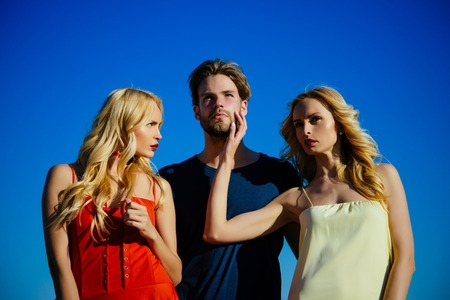Beauty and summer fashion. Love triangle and romance. Man with beard with twins, relations. Family trust, polygamy, betrayal, swinger. Twins women with macho on blue sky background. friendship