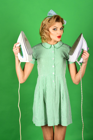 Funny girl ironing, retro woman hold iron on green background Stock Photo