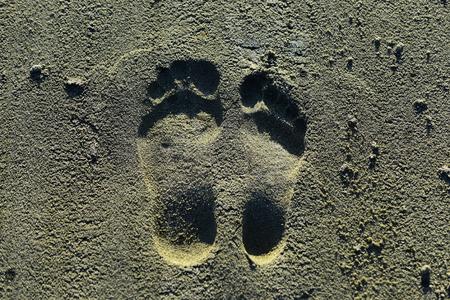 Footprints on sand. Human imprints, prints, tracks on sandy surface. Barefoot, feet, toes marks. Vacation, travel, wanderlust. Stock Photo - 109085223