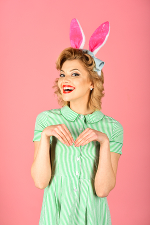 Easter, makeup, pinup party, girl in rabbit ears. Retro woman in bunny ears, easter. Pinup woman, vintage, look. Sexy blond girl with retro makeup, playboy. Beauty, fashion, cosmetics, vintage style. Stock Photo