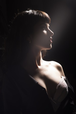 Girl with sensual face, naked shoulder and decollete in dark room. Sexy woman with full lips and breasts in lace bra. Night, beauty, mystery, tender, desire, fashion concept. Ray of light in darkness.