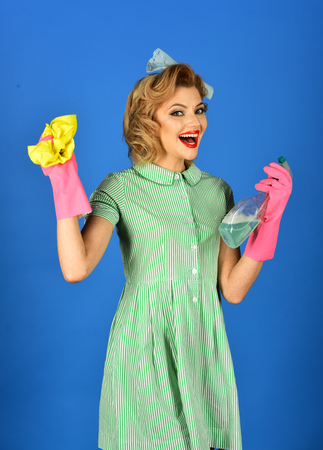 Housekeeper in uniform with clean spray, duster. Pinup woman hold soup bottle, duster. Cleanup, cleaning services, wife, gender. Retro woman cleaner on blue background. Cleaning, retro style, purity.