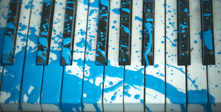 Piano with blue paint stain on the keyboard. Stock Photo