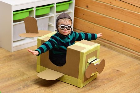 Pilot travel, airdrome, imagination. Air mail delivery, aircraft construction. Kid, pilot school, innovation. Dream, career, adventure, education. Little boy child play in cardboard plane, childhood. Фото со стока