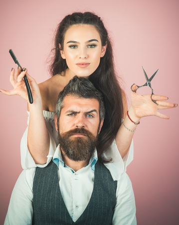 Happy positive woman and bearded man, hairdresser in the salon. Serious brutal man hairdresser making hairstyle for pretty woman in barber shop. Beautiful fashion couple