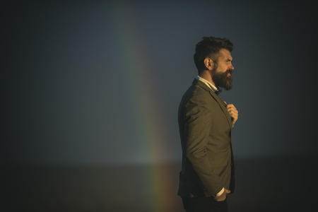 Successful man with scenery on background, side view. Guy with strict face in suit feels free and successful. Hipster with stylish appearance in front of sky with rainbow. Success and freedom concept.