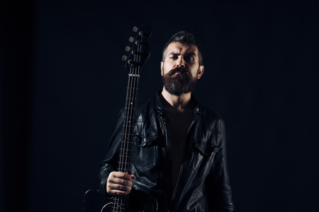 Young bearded man with electric guitar. Adult person hold instrument and play. Hobby, music concept, on grey Stock Photo - 105919364