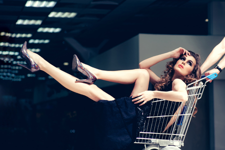 Sensual woman sit in shopping cart. Girl in fashionable dress, shoes in trolley in shop. Fashion, beauty, look, makeup. Shopper, shopaholic, shopping, shop. Sale, purchase, black Friday.