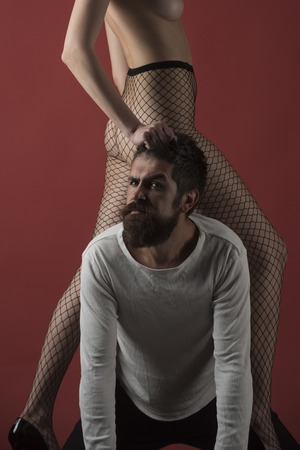 Dependence and henpecked concept. Female buttocks in fishnet tights on mans neck, burgundy background. Woman grabbed male hair, man in trap. Henpecked with strict face suffers from female caprice. Stock fotó